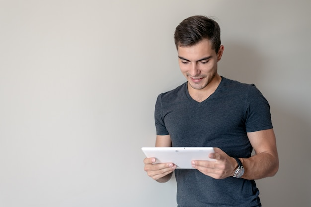 Man for conceptual. handsome young man uses a tablet standing at a gray wall, copy space