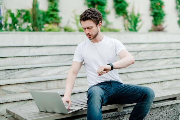 Man concerned about time working remotely as freelancer outdoors
