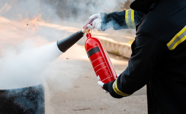 A man conducts exercises with a fire extinguisher. fire extinguishing concept. fire emergency incident