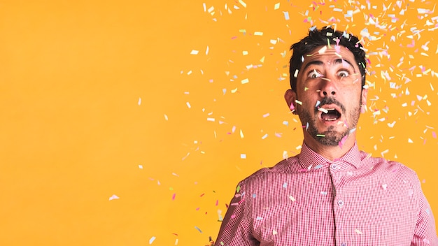 Man and confetti on orange background with copy space