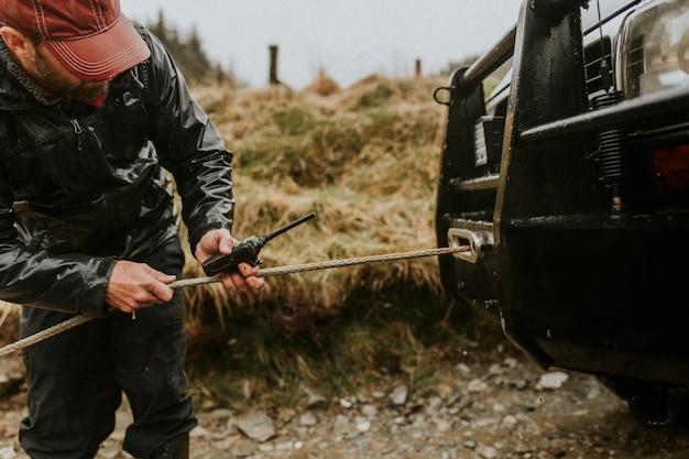 Человек, соединяющий автомобиль буксировочный трос