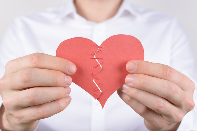 Man connecting two parts of paper heart