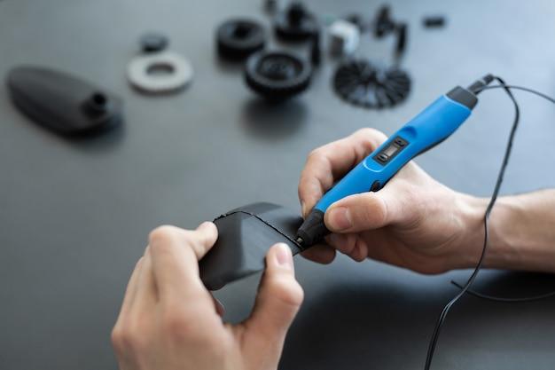 男は2つの3dプリンター部品を3dペンで接続します