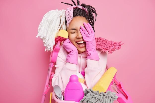 손으로 미소 짓는 남자 죄수 얼굴은 긍정적으로 재미 있고 집을 청소하는 동안 고무 장갑을 끼고 일요일을 보내고 세탁물 대야에서 방 포즈를 정리하는 데 깨끗한 장비를 사용합니다.
