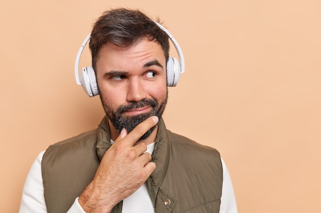Man considers something keeps hand on chin looks away wears wireless headphones on ears listens information dressed in vest isolated on brown