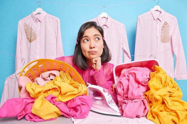 男はアイロン台の近くで何かポーズをとって、洗濯した洗濯物を広げて広げた