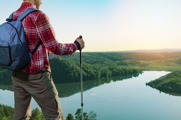 Man in contemplation, sunset, nature. man standing on a top of mountain, enjoying the beautiful sunset over a wide river valley.