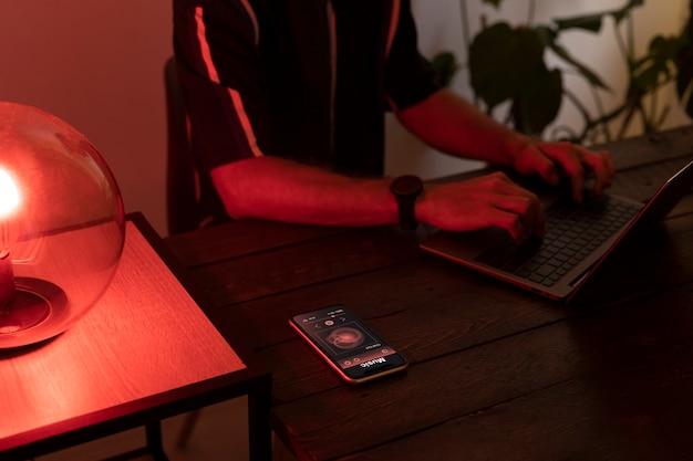 Человек, управляющий умной лампой со своего телефона