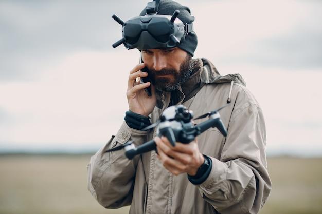 ゴーグルアンテナリモートコントローラーで航空写真とビデオ撮影のためのfpvクワッドコプタードローンを制御する男。