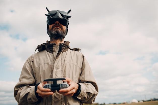 ゴーグルアンテナリモートコントローラーパッドで航空写真とビデオ撮影のためのクワッドコプタードローンを制御する男