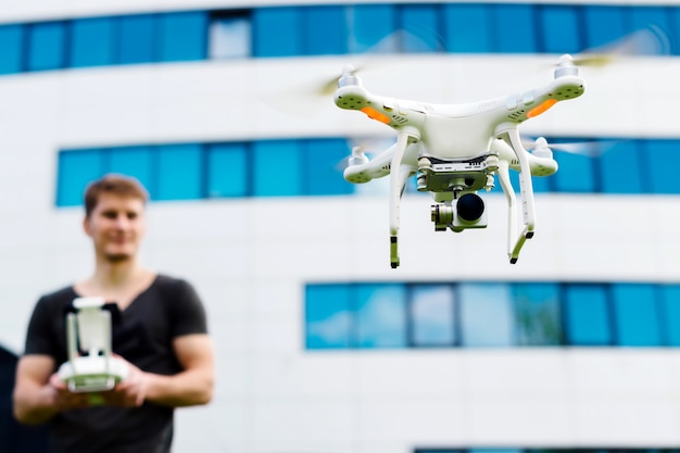 Man controls the drone in the city outdoors