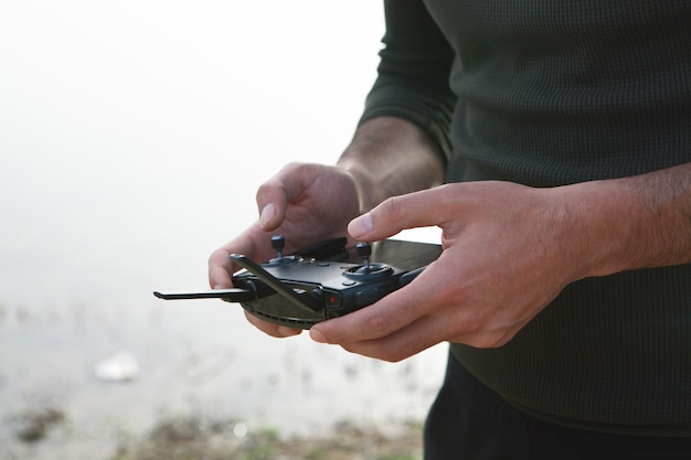 A man controls the drone's remote control during the day