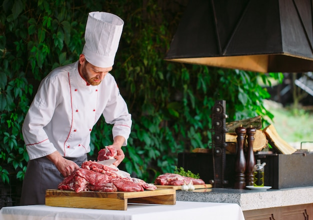 A man cook cuts meat with a knife in a restaurant.