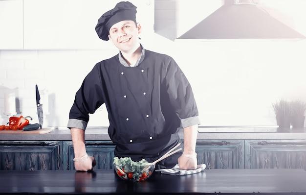 野菜の台所のテーブルで料理を準備する男料理人
