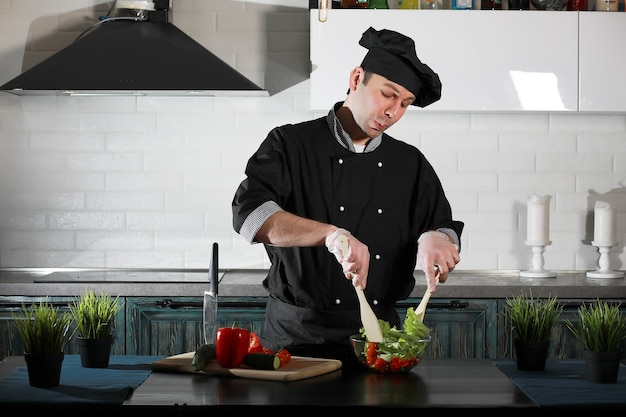 Man cook preparing food at the kitchen table of vegetables