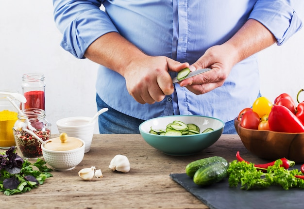 Мужчина готовит вегетарианский салат