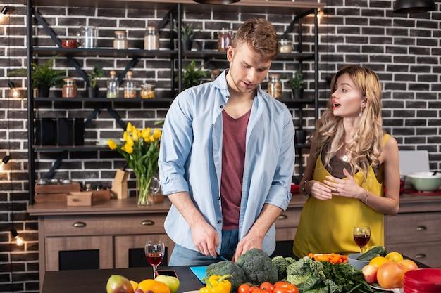 요리하는 남자. blonde-haired 매력적인 세련된 여자 친구가 부엌에 와서 그녀의 남자가 요리하는 것을보고