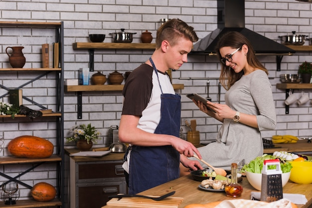 Man cooking dinner with woman sitting near