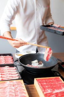 日本の和牛すき焼きセットを調理する男