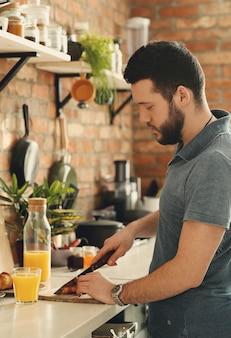 Uomo che cucina in cucina. mattina colazione