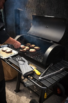 Of man cooking marbled meat on barbecue for burgers