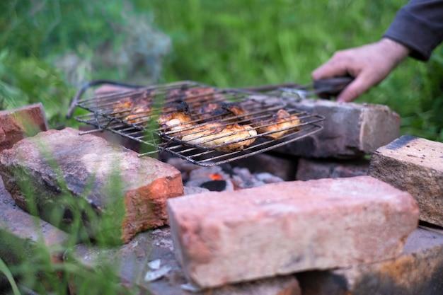 Мужчина готовит мясной шашлык на мангале в своем саду на простых кирпичах
