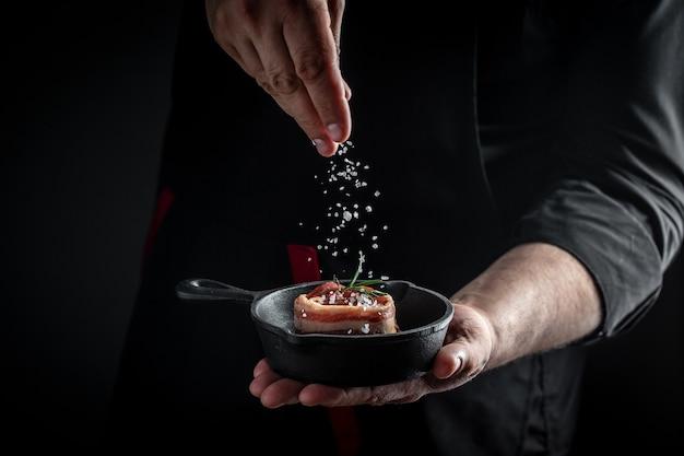 Человек готовит стейк из мяса. стейк из сырого филе миньон, покрытый беконом. стейки медальоны. баннер, рецепт меню.