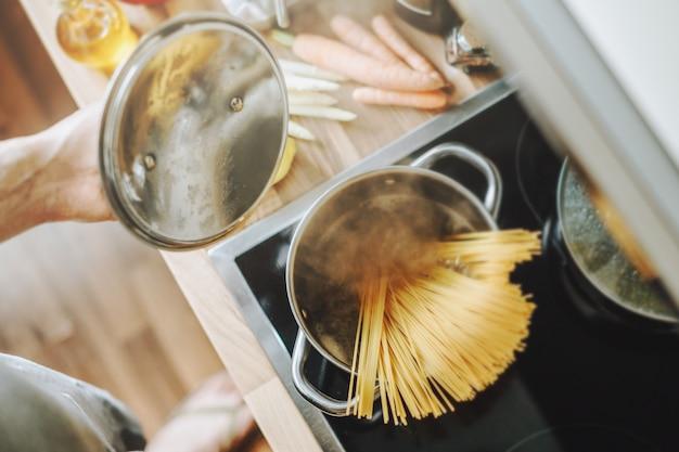 부엌에서 파스타 스파게티를 집에서 요리하는 남자. 가정 요리 또는 이탈리아 요리 개념.