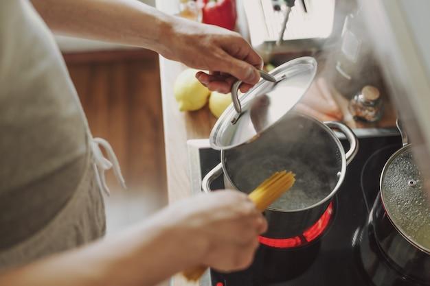 부엌에서 집에서 파스타 스파게티를 요리하는 남자.