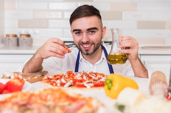 Man cooking pizza with tomatoes