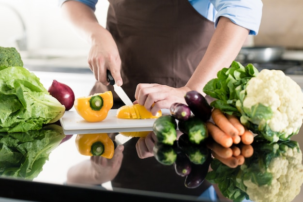 Man cooking and preparing salad in kitchen