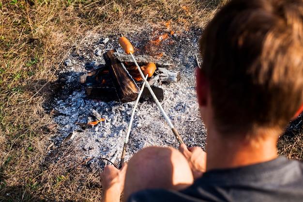 Man cooking sausages over the shoulder shot