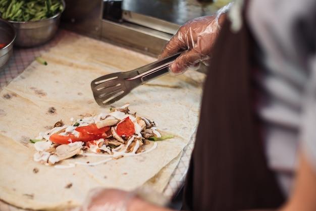 Man cooking shawarma in pita in the kitchen