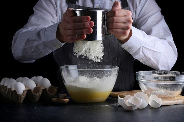 Человек готовит просеивание муки в луке