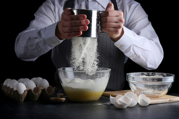 Человек готовит просеивание муки в миске
