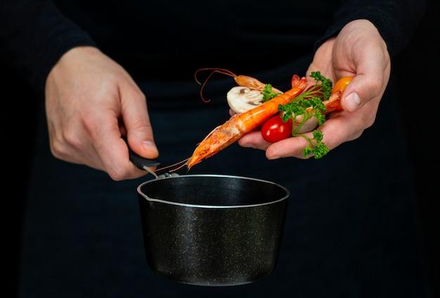 男は暗闇の中で鍋に新鮮なエビを調理します