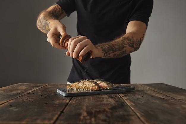男は素朴な木製のテーブルで健康的な食事を調理し、グリル用に準備された大理石のデッキにスパイスとハーブを添えた白ワインソースでサーモンの生の2つの部分をこしょう