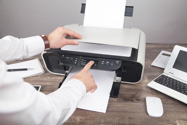 オフィスでドキュメントをコピーしてスキャンする男性。