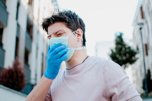 Человек кашляет в защитной маске на улице, страдает аллергией на загрязнение воздуха и болью в легких