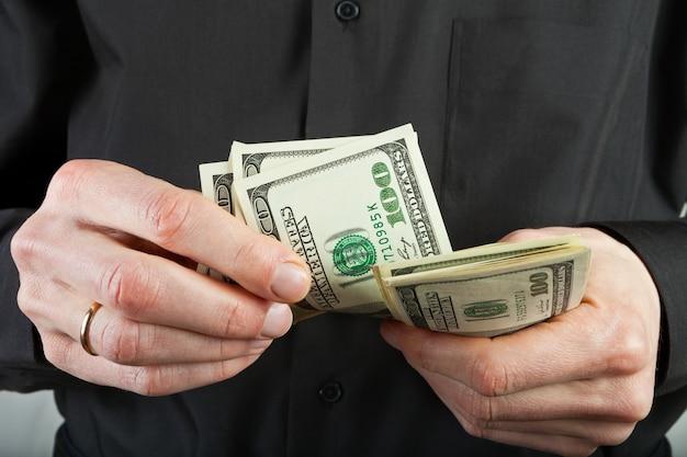 男は手でお金を数えるドルアメリカ