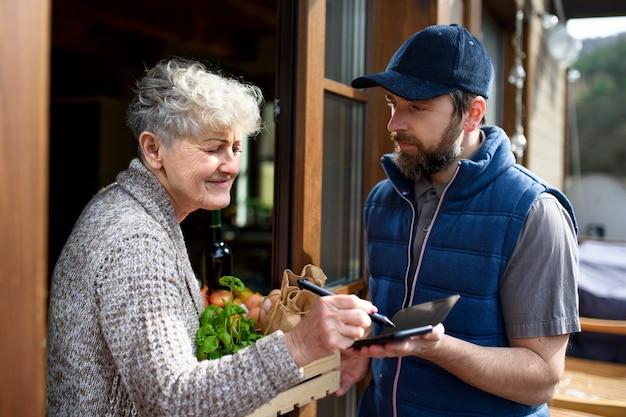 年配の女性に買い物を届ける男性宅配便、電子署名。