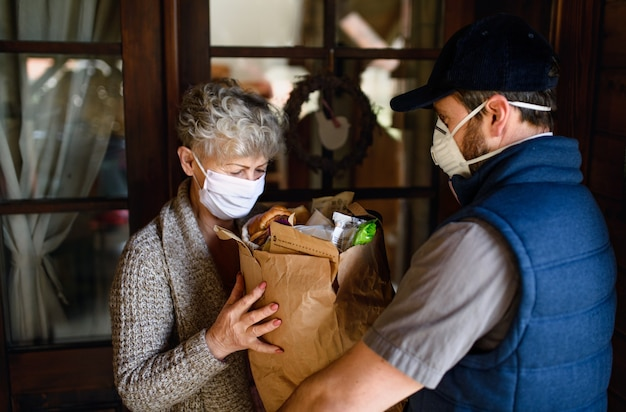 フェイスマスク、コロナウイルス、検疫のコンセプトで年配の女性に買い物を提供する男性宅配便。