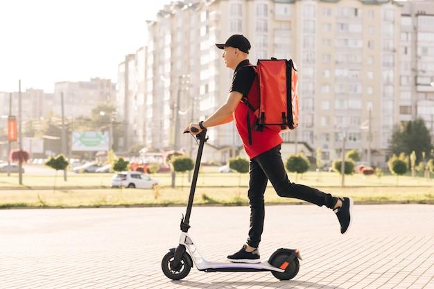 赤いサーマルバックパックを備えた男性宅配便の配達は、電動スクーターの配達で通りに乗ります