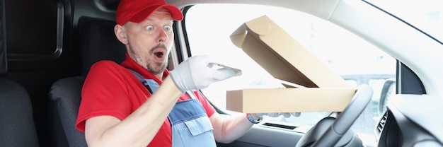 Человек-курьер крадет цифровой планшет из коробки в машине