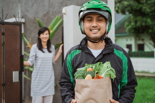 食料品の買い物を保持しているヘルメットを身に着けている男宅配便