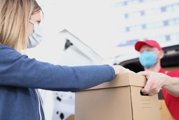 여자에게 골판지 상자를주는 보호 의료 마스크를 착용하는 남자 택배