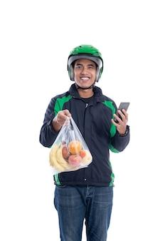 白い背景の上に分離されたビニール袋に食料品と男の宅配便