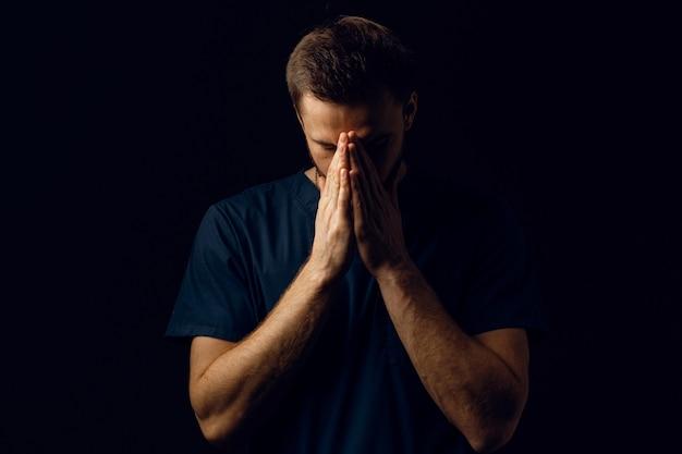 남자는 손으로 얼굴을 가리고 삶에 대해 생각합니다. 잘 생긴 남자는기도하고 하나님을 믿습니다. 정통 기독교 신앙.