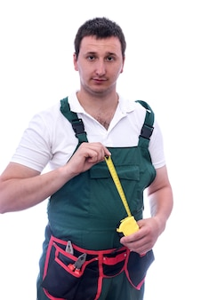 Man in coverall holding measuring tape isolated on white