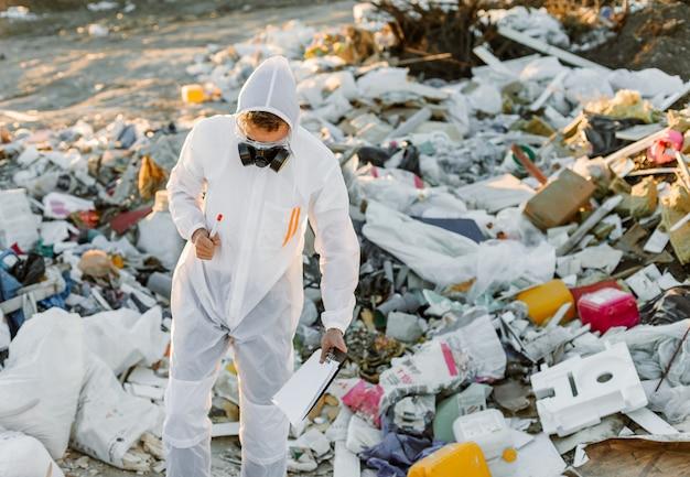 Uomo in tuta alla pillola della spazzatura, facendo ricerca